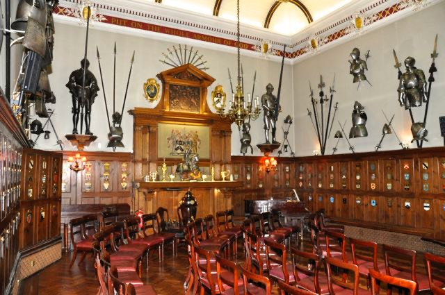 A photo of the interior of Armourers Hall featuring oak panelled walls, extensive heraldry, armour and medieval arms.