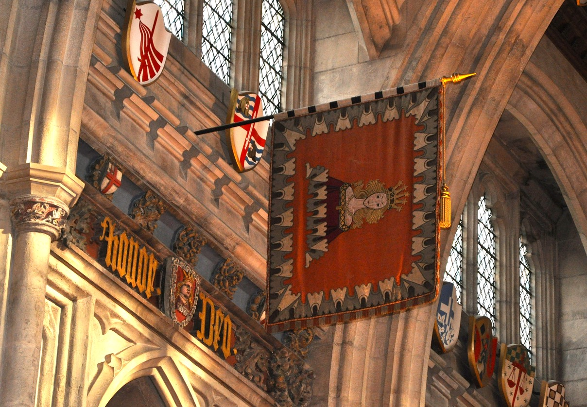 A photo of the house flag of the Mercers' Company hanging in Guildhall. Their flag is based upon their Coat of Arms featuring a crowned maiden rising from a cloud at her waist level.