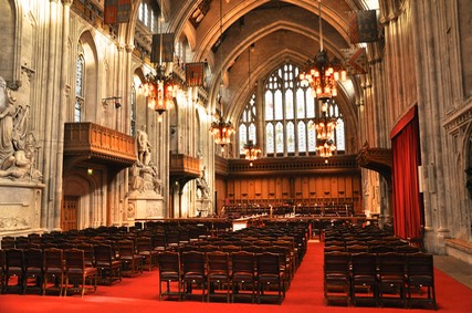 The interior of Guildhall laid out for a meeting of the Court of Common Council. Flags of the Great Twelve City Livery Companies hang from the walls.