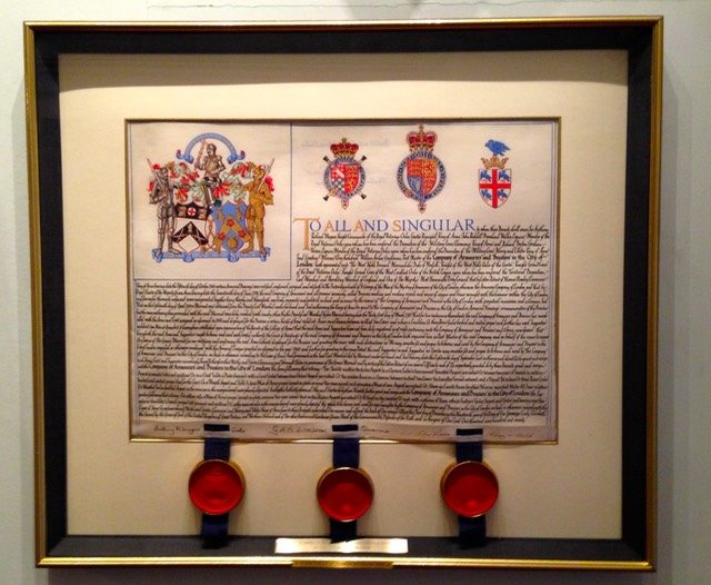 A framed Letters Patent granting a Coat of Arms to the Armourers' and Brasiers' Company. The Letters Patent is sealed with three wax seals, one for each of the Kings of Arms; Garter, Clarenceux and Norroy and Ulster