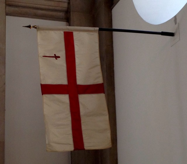 The flag of the City of London hanging in the Guild Church, St Lawrence Jewry. The flag is a simple red cross on a white background with a red sword of St Paul in the Canton (top left corner of the flag).
